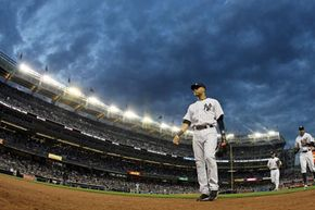 Derek Jeter of the New York Yankees walks to the dugout after an inning against the Tampa Bay Rays at Yankee Stadium. See more sports pictures.