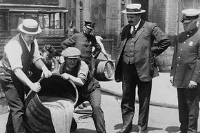 The New York City deputy police commissioner (right) watches agents pour liquor into a sewer following a raid during the height of Prohibition. The U.S. government also poisoned liquor to discourage illicit drinking.
