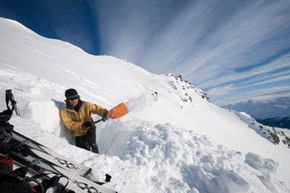 Man digs avalanche pit in snow before skiing downhill in Yukon backcountry.