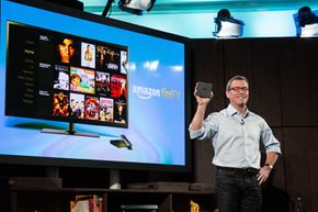 Amazon's vice president of Kindle, Peter Larsen, displays the Amazon Fire TV, which allows users to stream video, music, photos, games and more through their television.