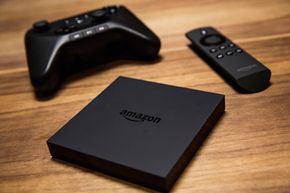 Pictured in the foreground is the Amazon Fire TV set-top box, along with its remote and gaming controller (sold separately).
