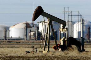 A pump jack works in a field near a Valero refinery in Sunray, Texas.