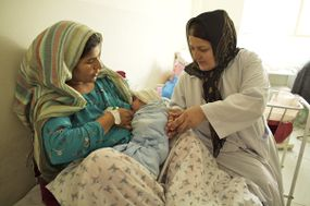 woman holding baby breastfeeding with doctor accompanying