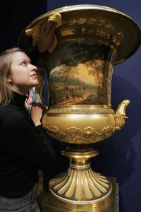 Christie's Employee, Sandra Nedvetskaia, carefully cleans a two-handled Campana vase, one of two, at Christie's Auction House in London, England.