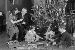 A father and his three children enjoy a model train at Christmas in the 1930s.