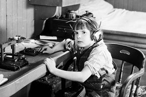 Actor Jackie Coogan looks a little scared to be using a telegraph machine in a scene from a 1924 movie.
