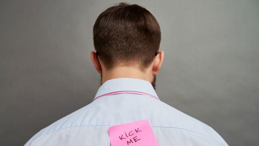 """man with """"kick me"""" sign"""