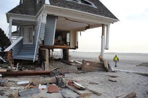 A debris engineer with the U.S. Army Corps of Engineers inspects a house devastated by Hurricane Sandy in Queens, N.Y.