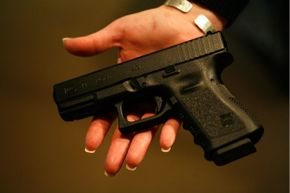 A woman holds a Glock 19, a 9 mm semi-automatic handgun. Both Jared Loughner and Cho Seung-Hui used this model during their respective mass shooting incidents.