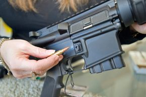 A California gun shop employee demonstrates how the 10-round magazine can be removed from a Stag Arms AR-15 type rifle using the tip of a bullet to depress the bullet button. It's one of the features that has made the rifle California legal.