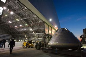 Workers move a simulated Orion crew module into a hangar at NASA Langley. The new module is intended as part of the Constellation program to land astronauts back on the moon and for the first time on Mars.