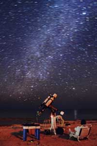 This astrophotographer relaxes on a Florida beach while his computer-driven telescope records the Orion Nebula.