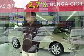 A car dealer in Jakarta, Indonesia, surveys the customers on his lot outside. See more small car pictures.