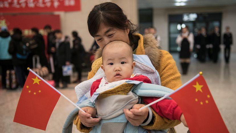 Baby holds flag during Chunyun travel rush