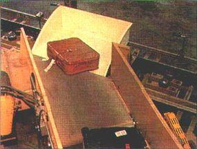 A conveyor shoots bags into moving DCVs.