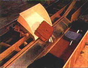 A DCV unloads a bag onto a conveyer.