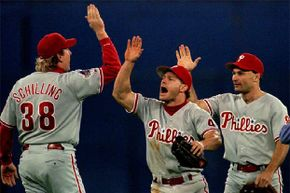 Philadelphia Phillies centerfielder Lenny Dykstra (C) high-fives pitcher Curt Schilling after the Phillies won Game 2 of the World Series in 1993. Dykstra later promoted himself as financial guru -- but still went bankrupt.