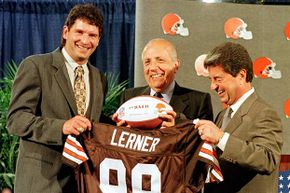 Owner of the Cleveland Browns Alfred Lerner (C) and former Cleveland Browns quarterback Bernie Kosar (L) hold up a team jersey and football at a press conference to announce that the team was again part of the National Football League in 1998.