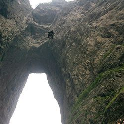 Daredevil Jeb Corliss bailed out of a helicopter and flew roughly 75 miles an hour through a 100-foot-wide hole in China's Tianmen Mountain.