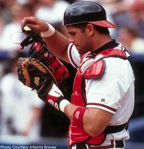 Former Atlanta Braves catcher Javy Lopez adjusts his chest protector and helmet.