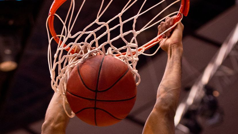 Basketball player dunks the ball with two hands.