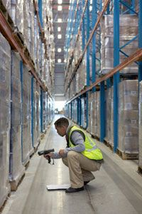 A warehouse worker uses a bar code scanner on pallets.