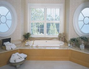 Deceptively simple, this tub surround in fine wood gains richness from the swirling grained marble top.