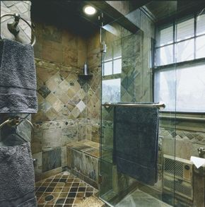 A shower stall with a frameless glass door lets the beauty of the bathroom's stone tiles show through.