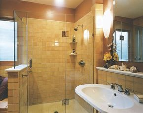 The golden tone of the walls is picked up in the tiles on the shower, walls, and floor of the welcoming bath.