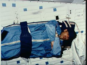Mission Specialist Fabian sleeps in zippered sleeping bag fastened to the middeck starboard wall on a 1983 mission.