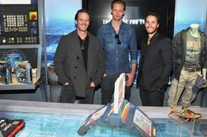 """""""Battleship"""" director Peter Berg (left) with actors Taylor Kitsch (right) and Alexander Skarsgard (center) and the Deluxe Battleship Movie Edition game at Hasbro's American International Toy Fair showroom in New York, February 13, 2012."""
