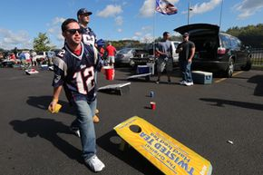 With beverage cup in hand, Joshua Pelletier of Haverhill, Mass. tosses a bean bag as he tailgates before a New England Patriots game in Foxborough, Mass. See other pictures of sports.