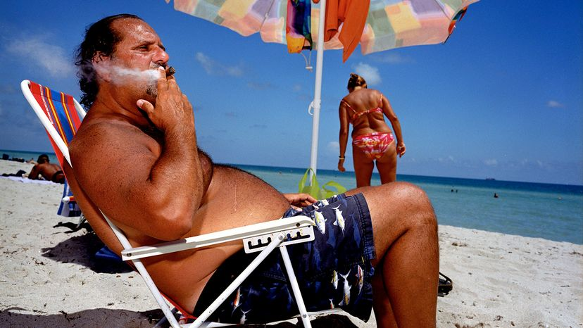 man smoking cigar on beach