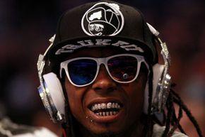 """2012年NBA全明星赛上,嘻哈歌手Lil' Wayne在场边戴着Dr. Dre设计的镶钻Beats耳机""""border="""