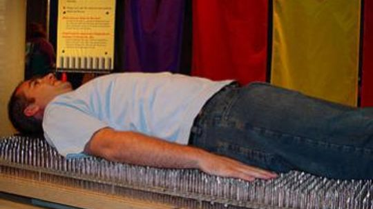 How can someone lie on a bed of nails without getting hurt?