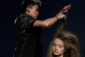 A stylist teases a model's hair.