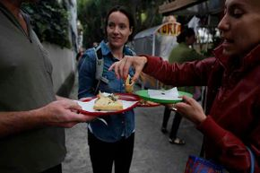 Eat Mexico guide Natalia Gris (R) splits quesadillas with tourists in Mexico City in 2013. Founded in 2010, Eat Mexico is the only culinary tour operator in the country that focuses exclusively on street food and markets.