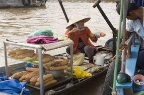 A banh mi vendor plies her wares from a boat in Vietnam.