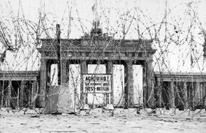 Barbed wire in front of the Brandenburg Gate, circa 1962. The sign warns that if you pass this point you leave West Berlin.