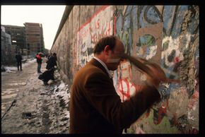 An unidentified man removes pieces of the Berlin Wall with a hammer Nov. 27, 1989, in East Berlin.