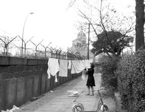 A German women hangs clothing out to dry on a line strung between a tree and the Berlin Wall, Nov.13, 1963.
