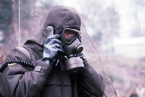 A typical full-face air-purifying respirator, used here with a hood and suit for extra protection