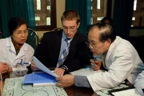 Medical epidemiologist Dr. Peter Horby (C) of the World Health Organization goes over statistics on Bird Flu with Vietnamese medical staff in 2004.