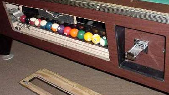 How does the ball return work on a coin-operated pool table?