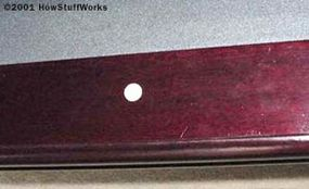 The cloth is made of wool and nylon. In this picture, you can also see one of the inlays. Inlays are normally made of mother-of-pearl or plastic, and are used as reference points in most billiards games.