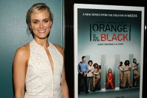 "Taylor Schilling, aka Piper Chapman on ""Orange Is the New Black,"" poses next to a promotional poster."