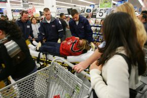Paramedics help a shopper who fell shortly after the doors opened at 5 a.m. on Black Friday, 2005 at the Wal-Mart in Duarte, Calif.
