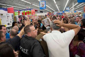 Shoppers who couldn't wait until midnight jostle and grab for cotton sheets at a Wal-Mart store shortly before 8 p.m. on Thanksgiving.