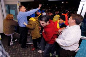 Best Buy general manager Terry Dilts (left) and assistant manager Robert Knowles (right) try to control the crowd at the front door to the Mesquite, Texas store.