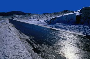 Black ice can form on a sunny (but below-freezing) day, when the sun warms up the road surface and any slushy stuff melts, despite the cold air temperature.